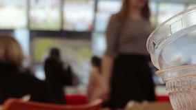 Defocused cafe scene dolly shot. Time lapse shot of crowd in mall food court view over table top with empty fast food