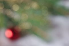 Defocused Christmas background. With bokeh and a red Christmas ball Royalty Free Stock Image