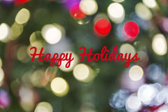 Defocused Christmas light background with Happy Holidays text. A defocused Christmas light background with Happy Holidays written across it in red text Royalty Free Stock Photography