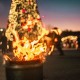 Defocused christmas tree. Fire to warm up and Christmas tree bokeh lights on the main square in Tirana, Albania during new year eve Stock Photography