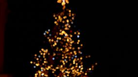 Defocused christmas tree with flashing lights. Camera is moving down stock video footage