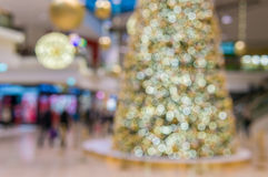 Defocused christmas tree in shopping center bokeh background.  Stock Photos