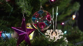 Defocused Christmas tree with star, ball and snowflake stock footage