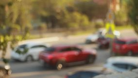 Defocused City auto traffic lights. Blurred picture at sunset day. Cars go and stand on the road. Focusing on a beautiful red car.  stock footage