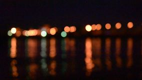 Defocused city lights reflected in water of river stock footage