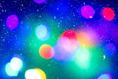 Defocused colorful ligths of Christmas tree. Multicolored bokeh lights during a snowfall. Stock Photos