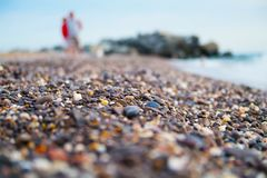 Defocused colorful sea pebbles with people on background. Macro shot Royalty Free Stock Photography