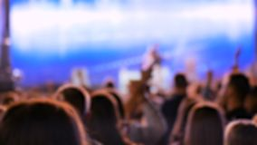 Defocused concert background. People partying at night open air concert in front of the stage. Nightlife and entertainment concept stock video