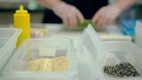 Defocused, CU: El cocinero prepara un rollo japonés con las semillas del arroz y de sésamo metrajes