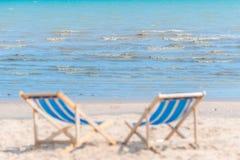 Defocused de sillas en la playa arenosa en buscar del día soleado fotografía de archivo