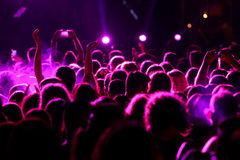 Defocused entertainment concert lighting on stage. Silhouettes of concert crowd in front of bright stage lights. motion image royalty free stock photo