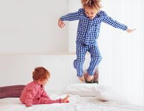 Defocused. excited kids, brothers playing in bedroom, jumping on bed in pajamas stock image