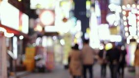 Defocused Film- Gesamtlänge Leute, die eine Nachtstraße gehen stock video