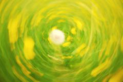 Defocused flowers and grass in circle background. Blurred and de focused yellow blossom and green grass Royalty Free Stock Photography
