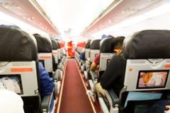 Defocused flygplankabininre med platser och passagerare Arkivfoto