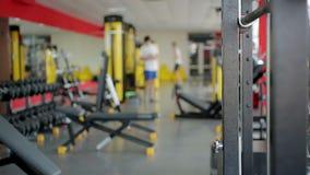 Defocused folk som använder sportutrustning för att öva i idrottshall på konditionklubban stock video
