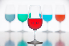 Defocused glasses of colored liquid. Photographed on a white background Stock Images