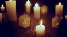 Defocused glowing candles and blinking decorative houses. On wooden table, over dark , zoom in video stock video footage