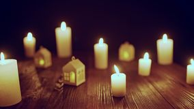 Defocused glowing candles and blinking decorative houses. Zoom in video from defocused glowing candles and blinking decorative houses on wooden table to the stock video footage