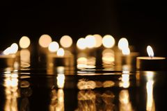 Defocused golden candlelight in darkness. Defocused candlelight with reflection in darkness Royalty Free Stock Photos