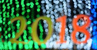 Defocused happy new year 2018 with bokeh lights background. Defocused multi-colored happy new year 2018 and bokeh lights background royalty free stock images