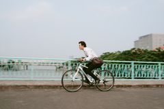 Defocused image of an active businessman riding a bicycle on the. Way to job Royalty Free Stock Photos