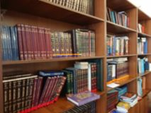 Defocused image. Multi-colored books on the bookshelf in the library. The bokeh effect Royalty Free Stock Photos