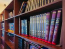Defocused image. Multi-colored books on the bookshelf in the library. The bokeh effect Royalty Free Stock Image