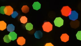 Defocused lights in the dark. Alternate with hot and cold colors. The brightness of New Year`s lamps passes through the seven-lens aperture of the lens stock video footage