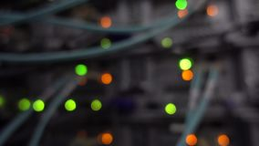 Defocused lights of working data servers with cables and flashing led lights.  stock video footage