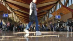 Defocused Low Angle Shot People at Airport Terminal. A low angle defocused shot of passengers walking around at a large airport`s terminal station stock video