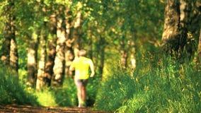 Defocused männlicher athletischer Läufer, der in den Wald läuft stock footage