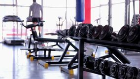 Defocused male silhouette warming up on treadmill before workout in the gym. Stock footage stock footage