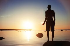 Magic of the sun. Man holding the sun reflection in hand. Defocused man silhouette catching round sun reflection in his hands. Vibrant colored outdoors Royalty Free Stock Photos