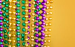 Defocused Mardi Gras beads against yellow background Stock Photo