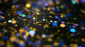 Defocused multicolored flikkeren schittert confettien, zwarte achtergrond Lichte vlekken van vakantie de abstracte feestelijke bo stock video