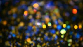 Defocused multicolored flikkeren schittert confettien, zwarte achtergrond Lichte vlekken van vakantie de abstracte feestelijke bo stock footage
