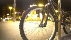 Defocused night city lights and pedestrians seen through bicycle wheel spokes stock video footage
