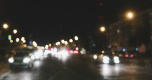 Defocused night traffic lights. Bluured cars lights dividing in two streams, pan left footage
