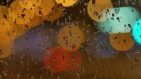 Defocused night traffic lights Through the glass in drops of rain. blur background. Moving bokeh circles of night. Blur background. Moving bokeh circles of night stock footage