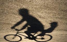 Defocused oskarp skuggakontur av en fader som rider en cykelintelligens arkivfoton