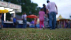 Defocused people at a fairground walking on overcast evening stock footage