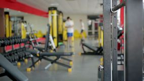 Defocused people using sports equipment for exercising in gym at fitness club