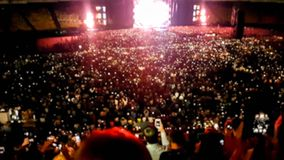 Defocused photo of people listening and watching big rock concert on music festival at big stadium. Crowd of fans. Defocused image of people listening and stock photo