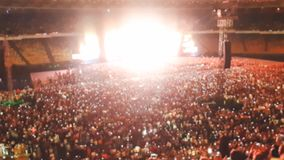 Defocused photo of people listening and watching big rock concert on music festival at big stadium. Crowd of fans. Defocused image of people listening and royalty free stock images