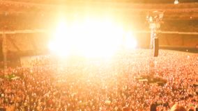 Defocused photo of people listening and watching big rock concert on music festival at big stadium. Crowd of fans. Defocused image of people listening and stock photography