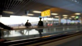 Defocused rulltrappa på flygplatsen, passagerare som rusar till porten, trans. arkivfilmer