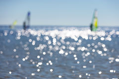Defocused seascape with windsurfers on sea surface Royalty Free Stock Image