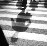 Defocused shadows of pedestrians crossing the street Stock Photos