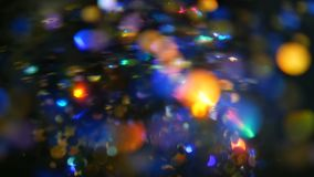 Defocused shimmering multicolored glitter confetti, black background. Holiday abstract festive bokeh light spots. Defocused shimmering multicolored glitter stock footage